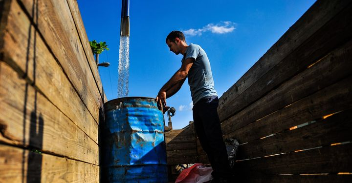 A man fills a drum with water in the Consolacion del Sur neighborhood in the Pinar del Rio province, Cuba on August 19, 2015.