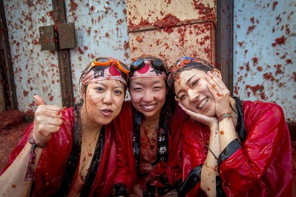 Revellers covered in tomato pulp pose during the annual 'tomatina' festivities in the village of Bunol, near Valencia on Augu