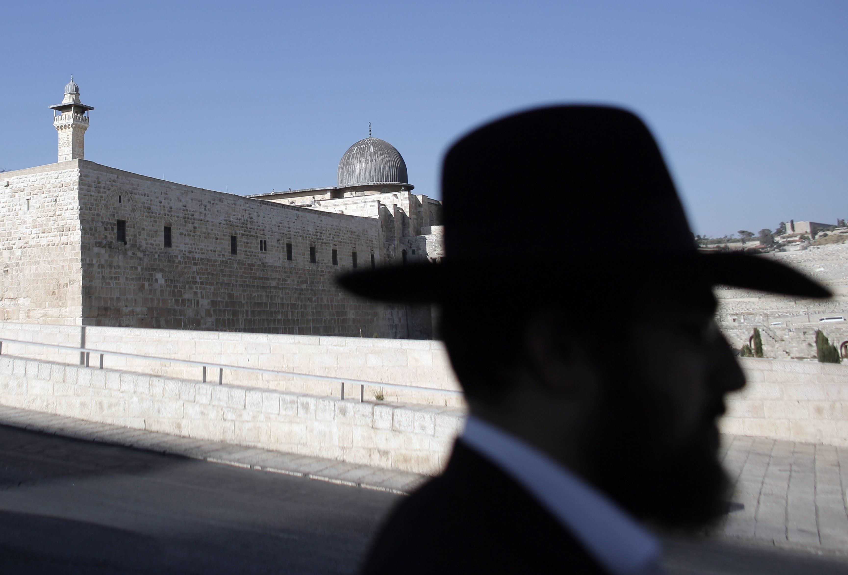 A picture shows the silhouette of an Orthodox Jew standing in the Jewish quarter of Jerusalem's Old City, backdropped by the dome of the al-Aqsa mosque, on July 14, 2015. AFP PHOTO /AHMAD GHARABLI        (Photo credit should read AHMAD GHARABLI/AFP/Getty Images)