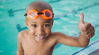 Cute little boy giving thumbs up at the pool at the leisure center