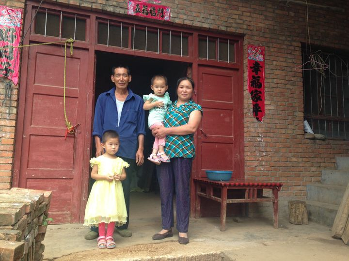Liu Qiaoyun (right) poses with her husband and two granddaughters. The family received weekly visits from family planning off