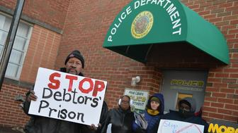 PINE LAWN, MO -  MARCH 5:  Demonstrators protest outside the police department entrance of the Pine Lawn Municipal Court Building on March 5, 2015  in Pine Lawn, Missouri.. The group of about 20 demonstrators were protesting the 20,000 outstanding arrest warrants issued last year in a town with 3,400 residents.  (Photo by Michael B. Thomas/Getty Images)