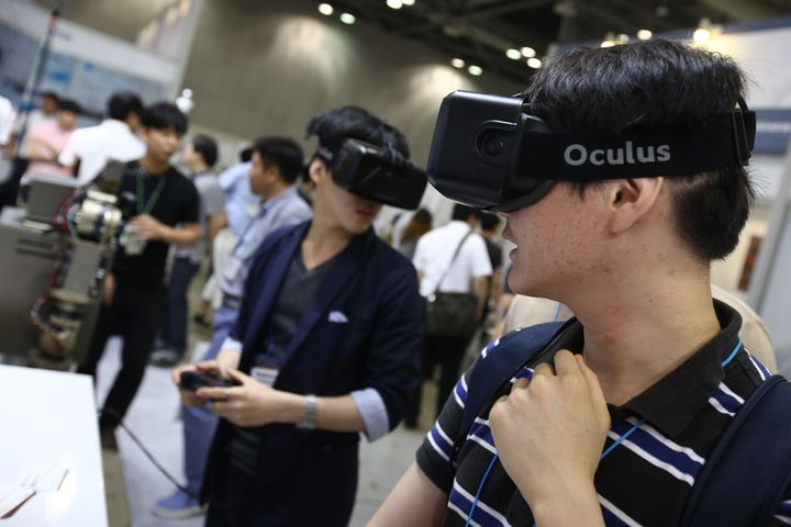 <span>Attendees wearing the Oculus VR Inc. Rift headset play video games at the RoboUniverse Conference &amp; Expo in Goyang,