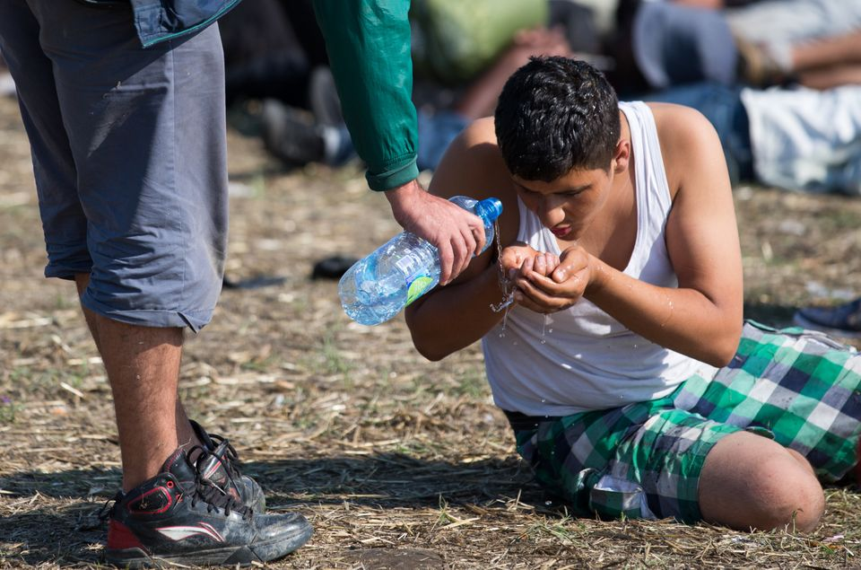 A man who had just crossed the Serbian-Hungarian border drinks water as he waits for buses taking migrants to be process