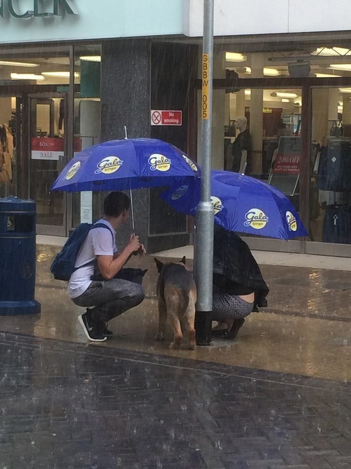 An onlooker from nearby Gala Bingo furnished the two with umbrellas.