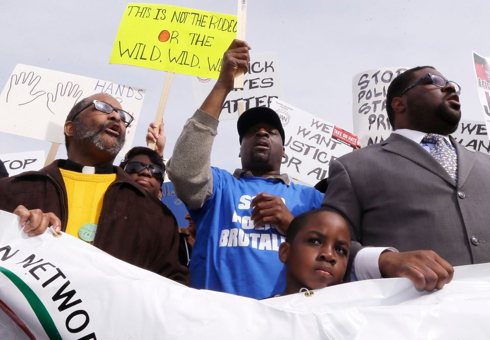 Floyd Dent, second from left, stands with protesters as they rally in front of the Inkster, Mich., police station Friday, Apr
