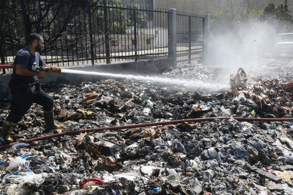 A firefighter sprays water on a trash pile that took fire in Beirut, Lebanon, on Aug. 28, 2015.