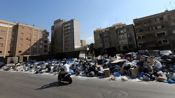 A man rides his motorbike past piles of trashin Beirut, Lebanon, on Aug. 27, 2015.