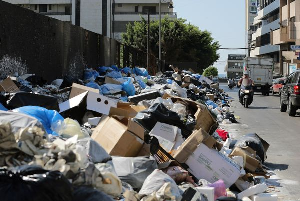 People drive past piles of trash in Beirut, Lebanon, on Aug. 27, 2015.