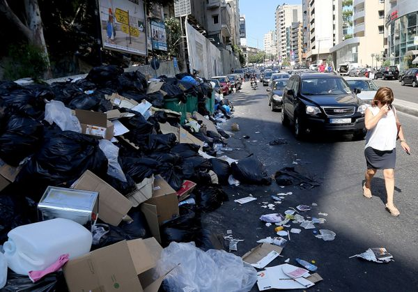 A woman covers her nose while walking past piles oftrashin Beirut, Lebanon, on Aug. 27, 2015.