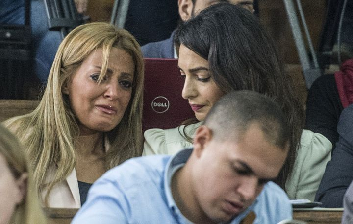 Marwa Fahmy (L), the wife of Canadian Al-Jazeera journalist Mohamed Fahmy (unseen), reacts as she sits next to Amal Clooney,