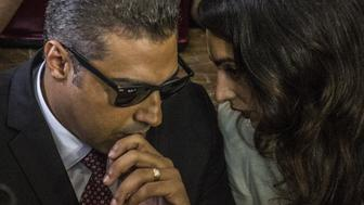Al-Jazeera journalist, Canadian Mohamed Fahmy (L), accused along with Egyptian Baher Mohamed of supporting the blacklisted Muslim Brotherhood in their coverage for the Qatari-owned broadcaster, talks to human rights lawyer representing him, Amal Clooney (R), during their trial in the capital Cairo on August 29, 2015. The court sentenced Fahmy and Mohamed, along with Australian journalist Peter Greste who was tried in absentia after his deportation early this year, to three years in prison in a shock ruling following global demands for their acquittal. AFP PHOTO / KHALED DESOUKI        (Photo credit should read KHALED DESOUKI/AFP/Getty Images)