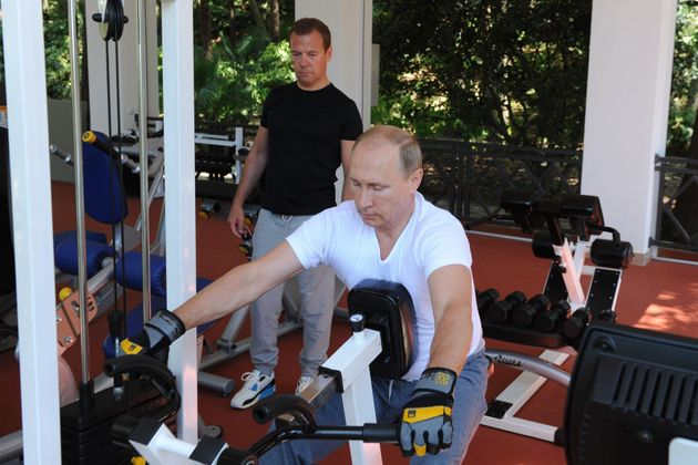 Russias President Vladimir Putin (C) and Russian Prime Minister Dmitry Medvedev work out at a gym at...