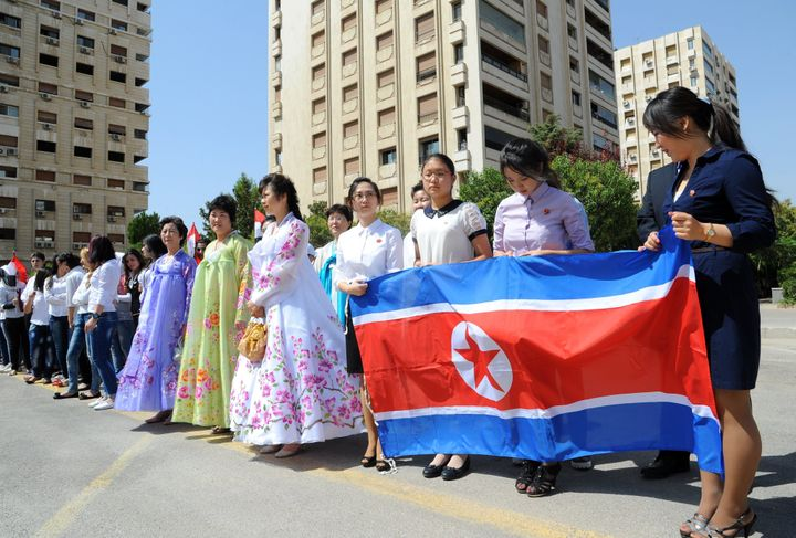 Young women hold a North Korean flag during a ceremony to name a park in Damascus after Kim Il Sung.