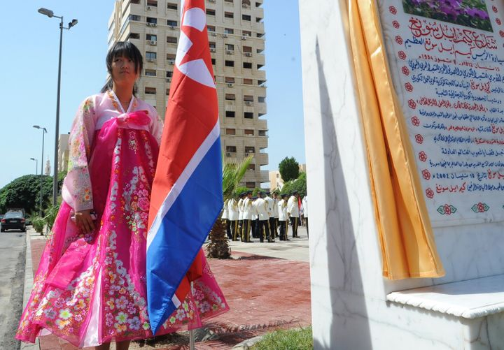 A young woman holds a North Korean flag during the inauguration ceremony of a park in the Syrian capital Damascus to honor No