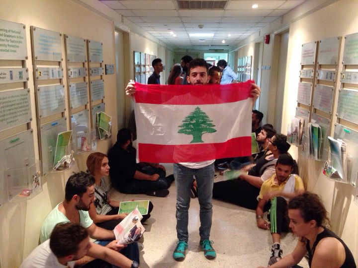 Lebanese activist holds a national flag in a hallway during a sit-in at Lebanon's environment ministry in Beirut on Sept.1, 2