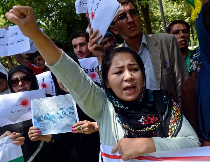 Afghan civil society activists protest anattack by Taliban militants in central Afghanistan in Kabul on July 27, 2014.&
