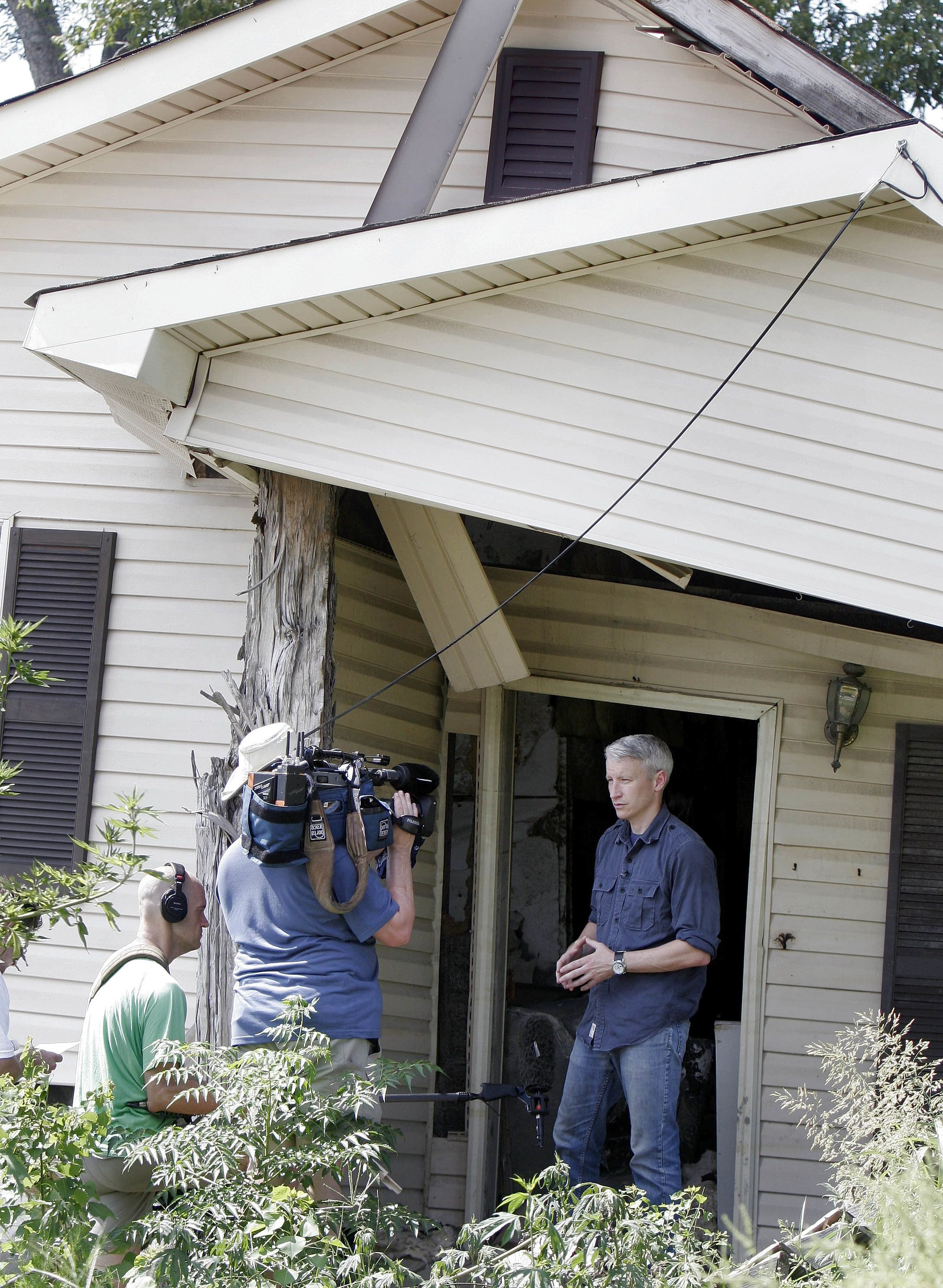 CNN's Anderson Cooper does some taping in the doorway of a house in the Lower Ninth Ward that was damaged by Hurricane Katrina nearly one year ago in New Orleans on Monday, Aug. 28, 2006. The national and international media have come to the region for the anniversary of Hurricane Katrina, however Cooper has returned to the region repeatedly.(AP Photo/Alex Brandon)