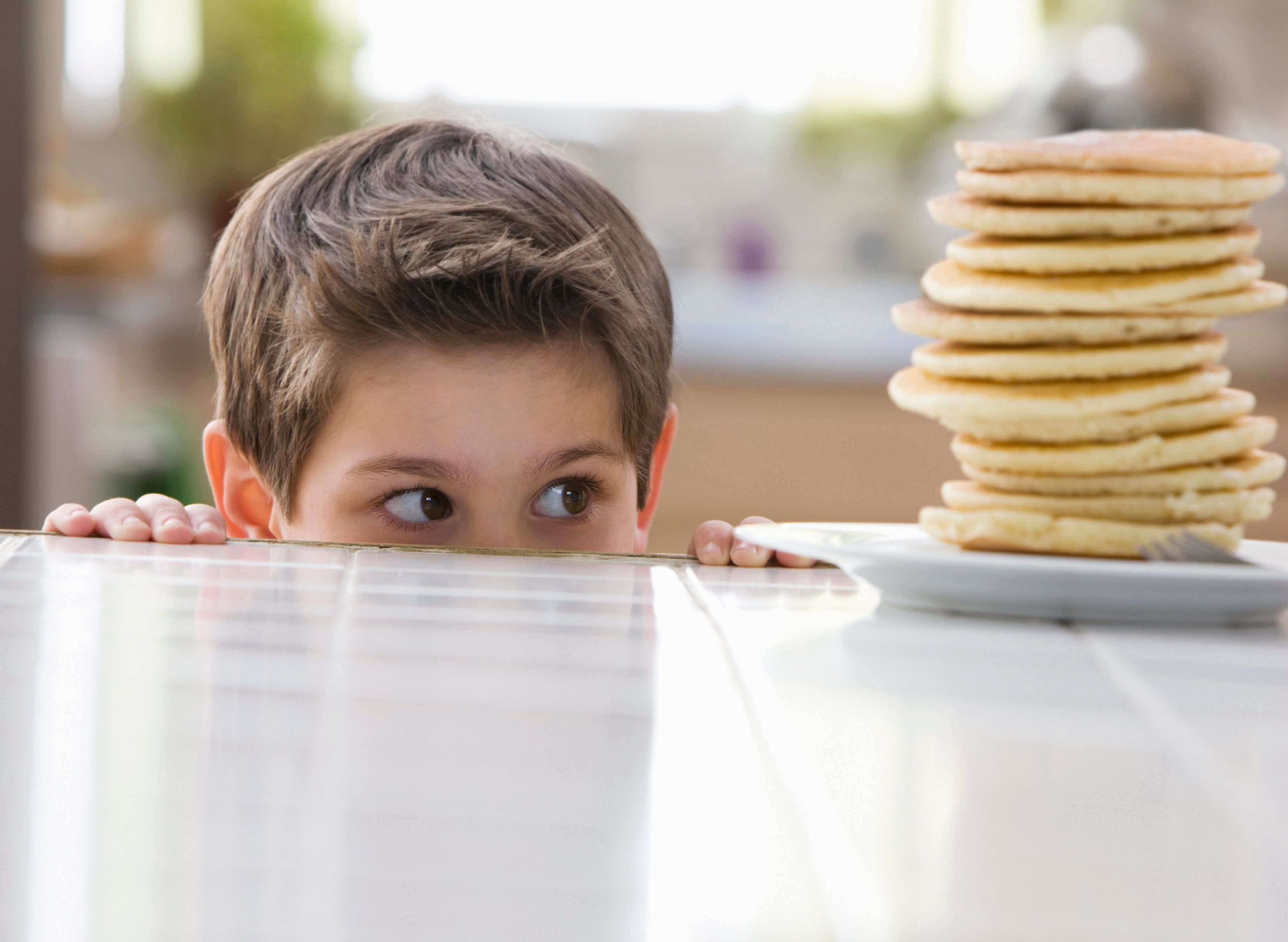 Caucasian boy looking at stack of pancakes