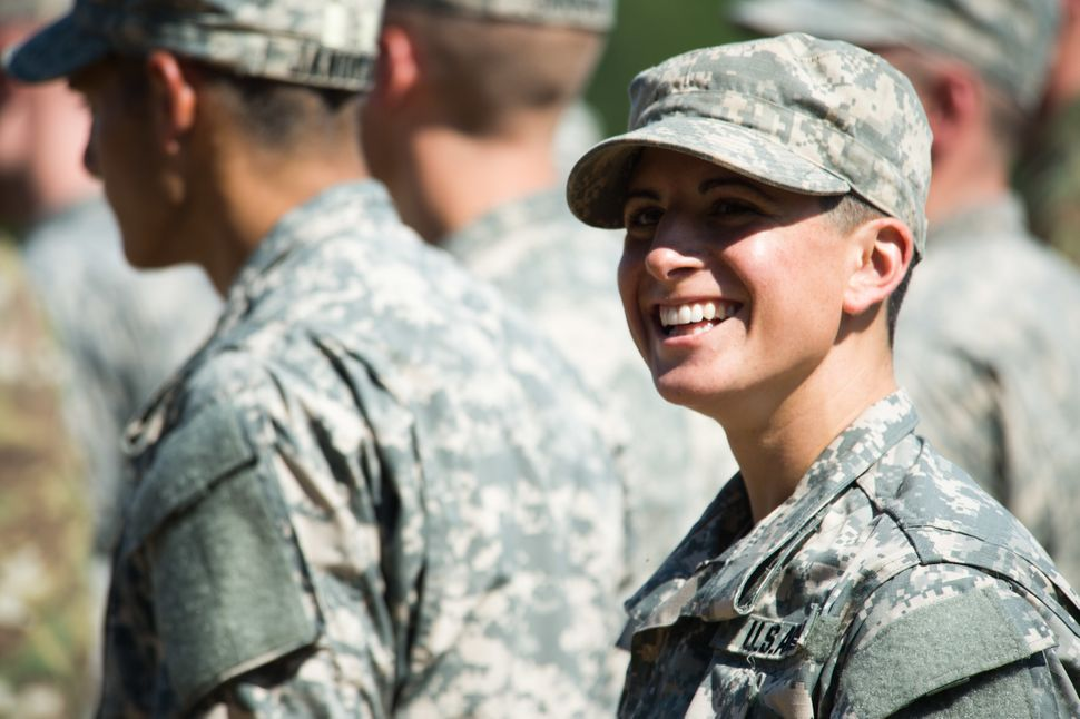 Capt. Kristen Griest smiles at friends and family as she waits with her U.S. Army Ranger School Class 08-15 to graduate at Fo