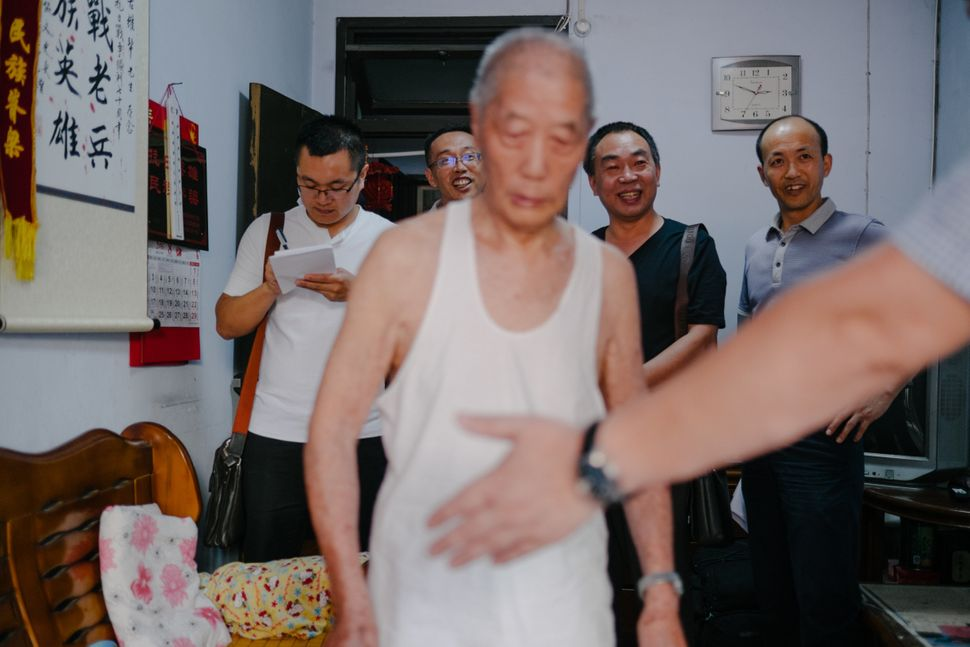 Local officials visit Zheng Weibang to check if he is healthy enough to travel to Beijing. He will receive a medal of honor f