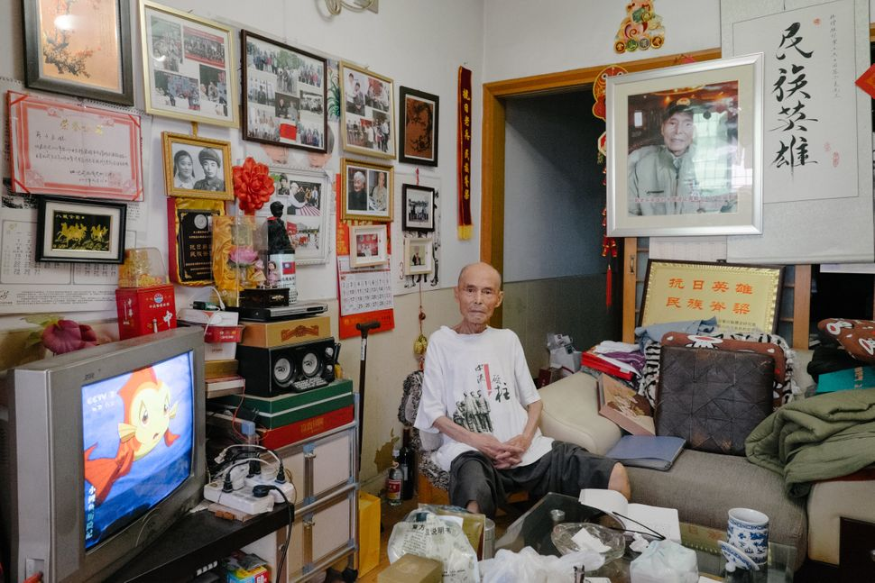 On the walls of Su's living room in Chengdu hang photos and certificates commending his service.