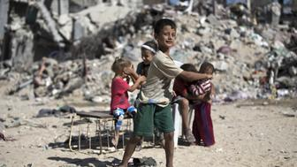 <p>Palestinian children play next to the rubble of buildings in Gaza City's eastern suburb of al-Shejaiya on Aug. 25, 2015.</p>