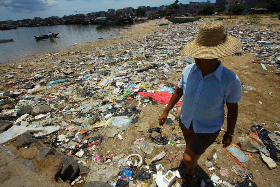 A Chinese farmer walks along a garbage-strewn beach in Anguan village, Hainan, China, on June 13, 2011.