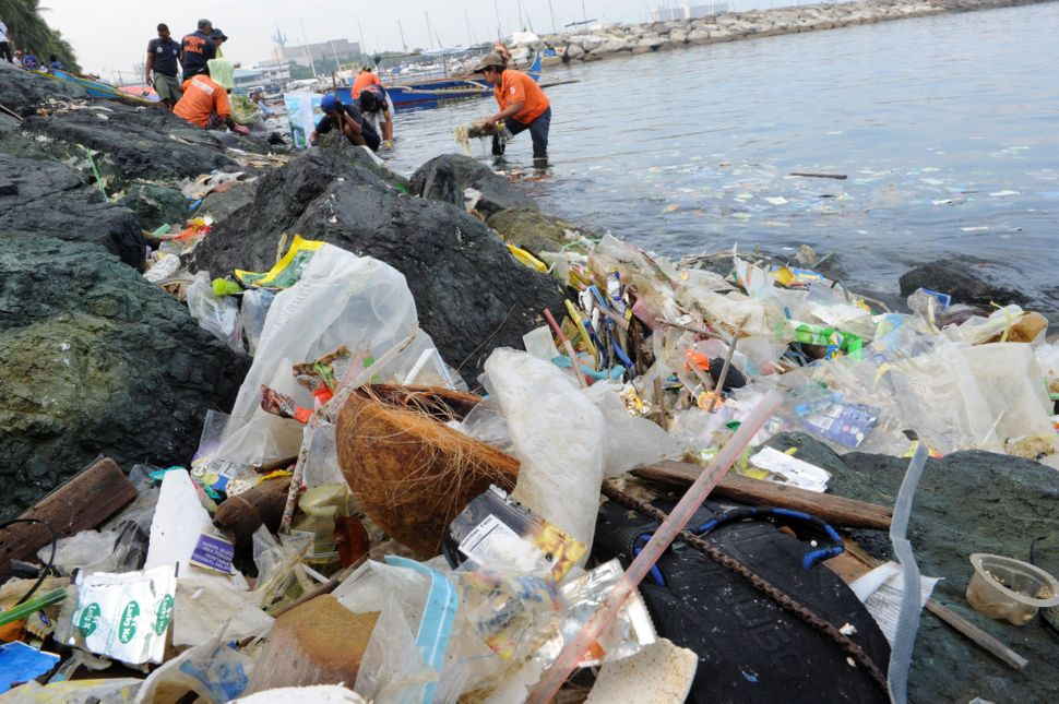 People collect plastic bags and other types of garbage from the Manila Bay on July 3, 2014.