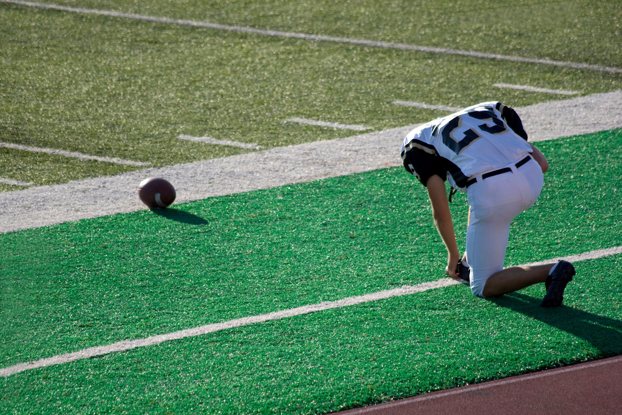 'Football player prays on the sidelines before a game. Color space is ProPhoto, RGB, processed from a 16 bit RAW image.View Similar Images Here:'