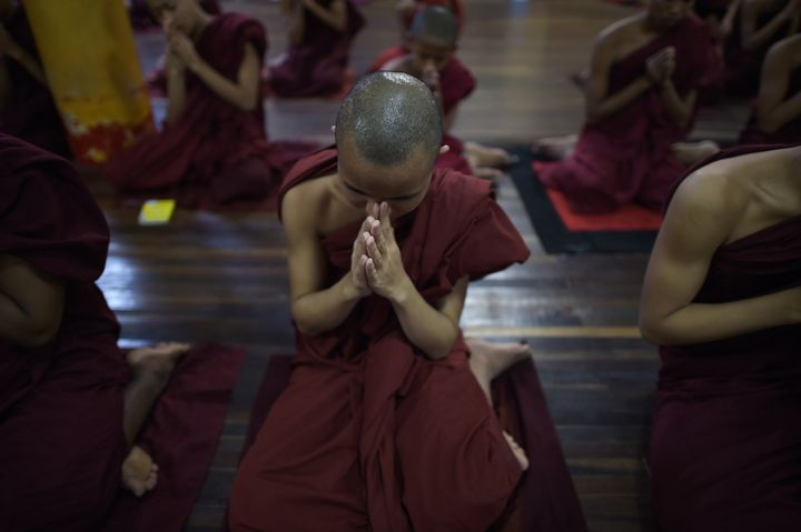 This picture taken on June 24, 2015 shows Buddhist novices praying at a monastery affiliated with the Ma Ba Tha organization