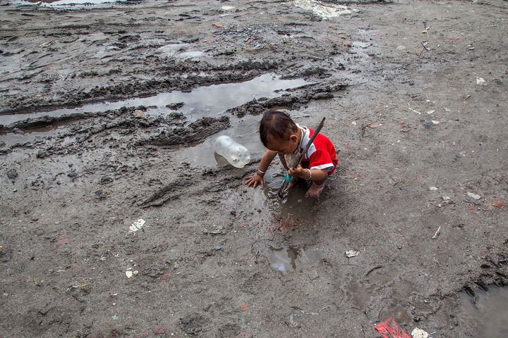 KATHMANDU, NEPAL - AUGUST 13: A young boy plays in the mud in a flooded lane inside the Chuchepati displacement camp on