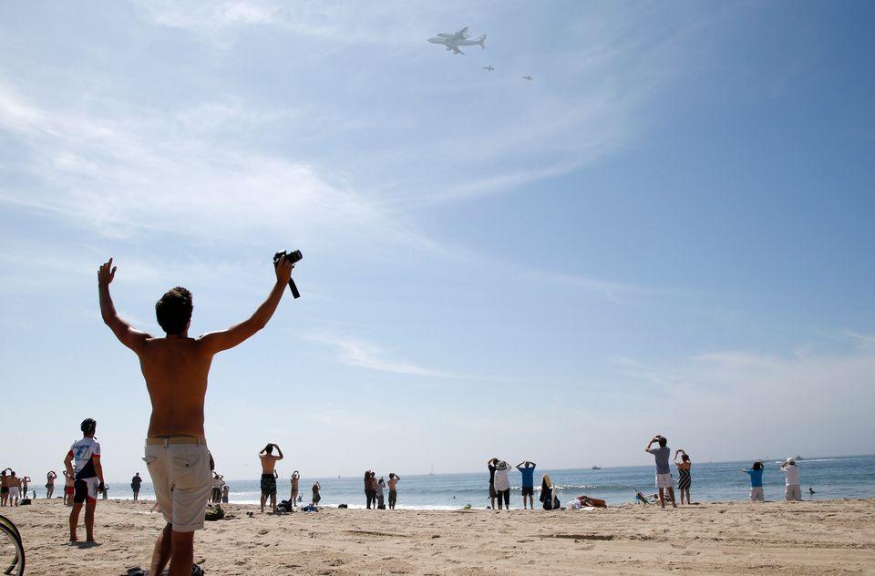 Spectators watch as the Space Shuttle Endeavour mounted on NASA's Shuttle Carrier Aircraft (SCA) flies near Santa Monica, Cal