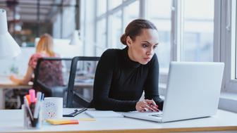 Image of woman using laptop while sitting at her desk. Young african american businesswoman sitting in the office and working on laptop.