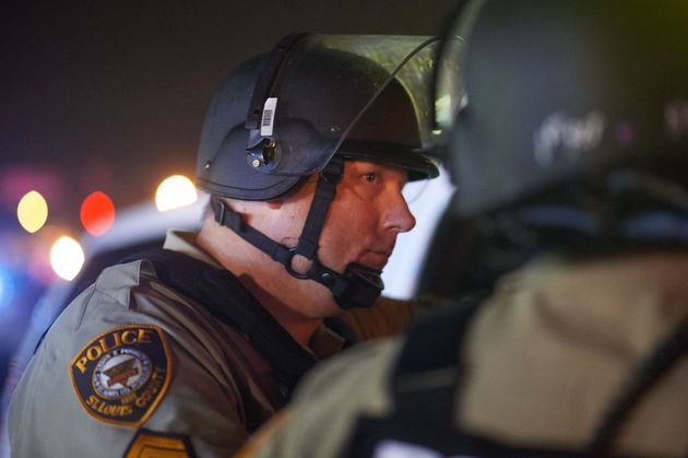 "<span class='image-component__caption' itemprop=""caption"">Police officers in Ferguson monitoring protests one year after 18-year-old Michael Brown was shot and killed by officer Darren Wilson. </span>"