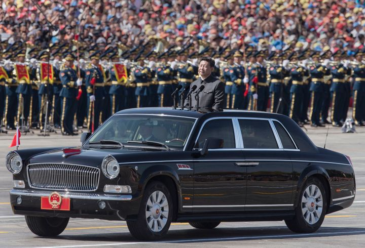 Chinese president and leader of the Communist Party Xi Jinping rides in an open top car in front of Tiananmen Square and the