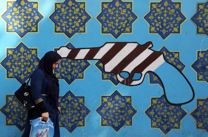 A woman walks past graffiti in Tehran on Sept. 2, 2015.