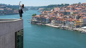 <p>Woman shooting dangerous selfie with city view.&nbsp;</p>