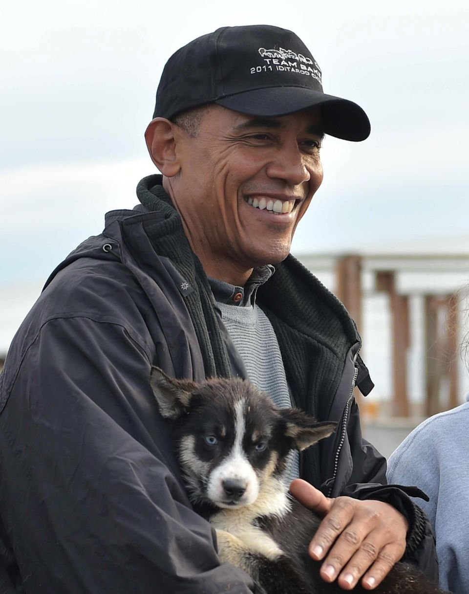 President Barack Obama holds a puppy while visiting musher John Baker and his family in Kotzebue, Alaska, on Wednesday.