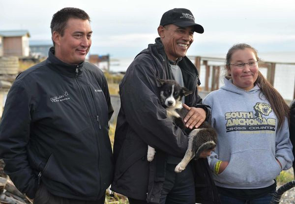 Obama holds a puppy while posing for a photo with musher John Baker (left) and a family member in Kotzebue, Alaska.
