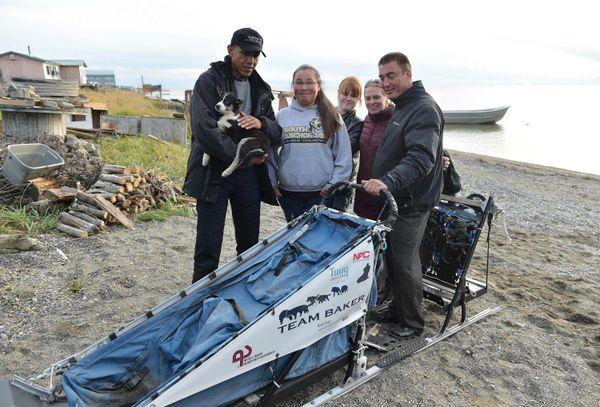 Obama talks with 2011 Iditarod champion John Baker (right) andhis family in Kotzebue, Alaska, on Wednesday.