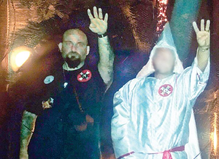 <span>In this photo from&nbsp;the Jennings Daily News, Raymond Mott, left, is seen giving a Nazi salute at a Ku Klux Klan ral