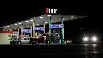 Motorist purchase gas at a station that dropped the unleaded fuel price to $1.99 per gallon, Wednesday, Aug. 26, 2015, in San Antonio. The price of oil fell back below $39 a barrel after a U.S. government report showed an unexpected decline in demand for gasoline last week. (AP Photo/Eric Gay)
