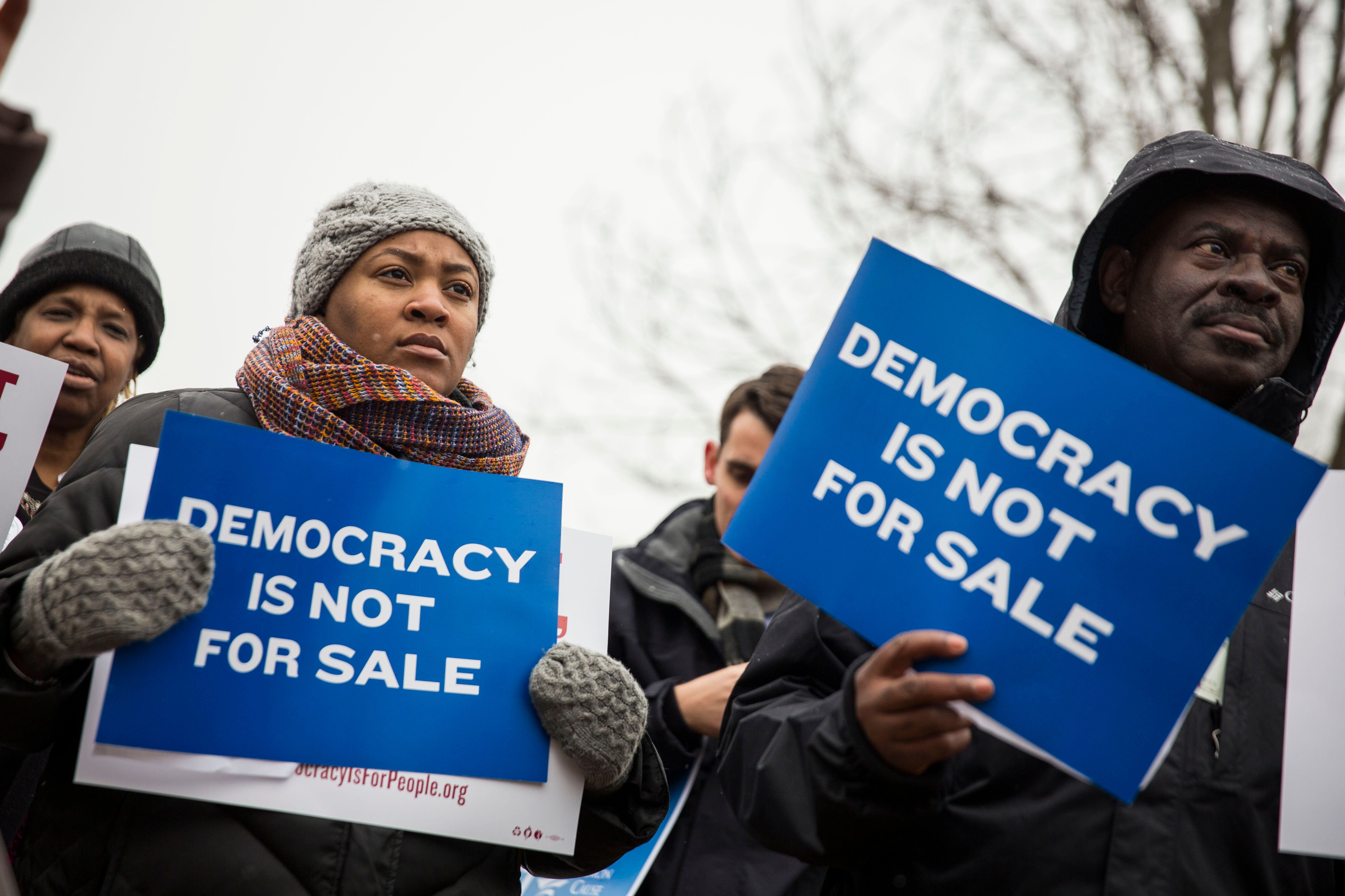 WASHINGTON, DC - JANUARY 21: Attendees hold signs as they listen to speakers during a rally calling for an end to corporate money in politics and to mark the fifth anniversary of the Supreme Court's Citizens United decision, at Lafayette Square near the White House, January 21, 2015 in Washington, DC. Wednesday is the fifth anniversary of the landmark ruling, which paved the way for additional campaign money from corporations, unions and other interests and prevented the government from setting limits on corporate political spending. (Photo by Drew Angerer/Getty Images)