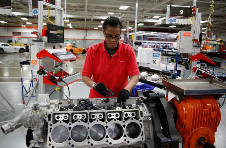 A Fiat Chrysler employee works on a 2015 Dodge Viper car engine at a Detroit, Michigan factory in May 2015. Economists d