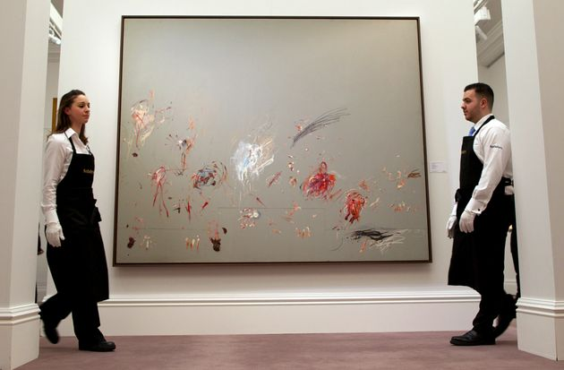 Sotheby's employees walk past a newly-discovered painting by Cy Twombly during the Sotheby's Impressionist,...