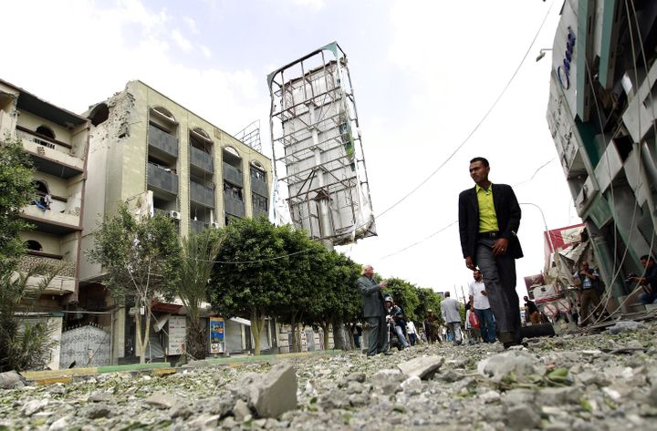 A Yemeni man walks past damaged buildings following air-strikes by the Saudi-led coalition in the capital Sanaa on Sept. 5, 2