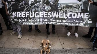 People hold a banner reading '#Refugees welcome' on September 6, 2015 during a rally in support of Syrian refugees at the place de la Comedie in Lyon. Germany and France have agreed that the European Union, facing an unprecedented influx of migrants, should impose binding quotas on the numbers member states take in, German Chancellor Angela Merkel said on September 3, 2015. The head of the United Nations refugee agency Antonio Guterres said today that while Europe's asylum system was dysfunctional, the migrant crisis was 'manageable' if countries worked together. AFP PHOTO / JEAN-PHILIPPE KSIAZEK        (Photo credit should read JEAN-PHILIPPE KSIAZEK/AFP/Getty Images)