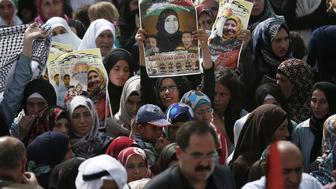 <p>Palestinian women hold placards during the funeral of Riham Dawabsha in Duma, West Bank on Sep. 7, 2015.</p>