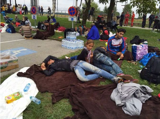Weary travelers collapse on the grass outside Nickelsdorf train station in Austria.
